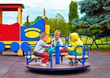 Trois petits amis, enfants ayant l'amusement sur le rond point au terrain de jeu Images libres de droits