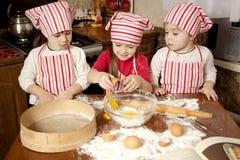 Trois petits chefs dans la cuisine Photo stock