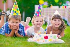 Trois petits enfants célébrant l'anniversaire Photographie stock libre de droits
