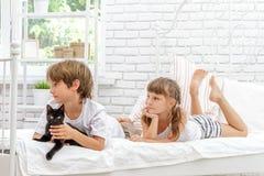 Trois petits enfants heureux jouant avec le chat sur le lit blanc à h image stock