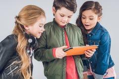 Trois petits enfants mignons à l'aide du comprimé numérique ensemble Image stock