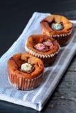 Trois petits gâteaux au fromage délicieux avec du chocolat fondu et le glaçage coloré de fleurs de sucre Image stock