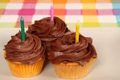 Trois petits gâteaux givrés par chocolat avec des bougies photos libres de droits