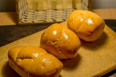 Trois petits pains de pain à l'ail sur un conseil en bois comme addition à un plat photos libres de droits