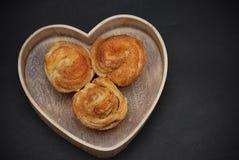 Trois petits pains de petit pain doux de cannelle au coeur en bois, au-dessus du fond noir Amour pour des desserts et Confectiona Images libres de droits