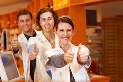 Trois pharmaciens retenant des pouces vers le haut Photographie stock