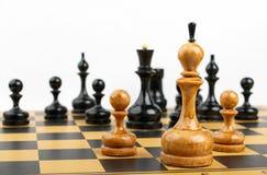 Trois pièces d'échecs blanches vis-à-vis des chiffres noirs Images libres de droits