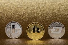 Trois pièces de monnaie de cryptocurrency, bitcoin d'or, litecoin argenté et tiret inventent, sur le fond d'or scintillant image stock