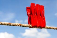 Trois pinces à linge en plastique rouges et une blanchisserie garnissent de bleu trouble Photographie stock