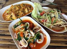 Trois plats de cuisine thaïlandaise de fruits de mer sur le fond en bambou de table photographie stock