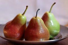 Trois poires, poires se trouvant du plat, poires vert rouge Photos libres de droits
