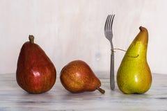 Trois poires sur une table en bois Photos conceptuelles Une poire avec une fourchette Composition avec des poires Trois poires Image stock