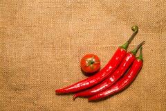 Trois poivrons du Chili et tomat de cerise sur le tissu très vieux Image stock