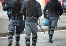 Trois policiers avec la veste anti-à l'épreuve des balles dans l'unifor d'anti-émeute Photo stock