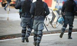 Trois policiers avec les gilets à l'épreuve des balles s'ameutent dans le tapotement uniforme Image libre de droits