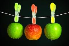 Trois pommes avec des pinces à linge dans une ligne image stock