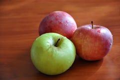 Trois pommes colorées sur la table image stock
