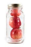 Trois pommes dans un choc de maçon en verre pour la mise en boîte Image stock