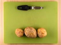 Trois pommes de terre non épluchées sur le conseil de plastique vert Images libres de droits