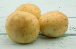 Trois pommes de terre sur le bois de vert de mer Images stock