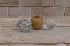 Trois pommes de verre et de bois, sur la voie de la pierre Images libres de droits