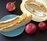 Trois pommes et morceaux rouges de melon du plat et coupé les fleurs de melon à côté d'Astra Photo stock