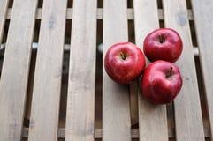 Trois pommes rouge foncé sur la vue supérieure extérieure en bois Image libre de droits