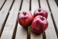 Trois pommes rouge foncé sur la vue supérieure extérieure en bois Images stock