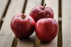 Trois pommes rouge foncé sur la vue supérieure extérieure en bois Photographie stock libre de droits
