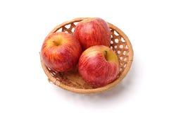 Trois pommes rouges dans un panier en osier d'isolement sur un fond blanc Photo libre de droits