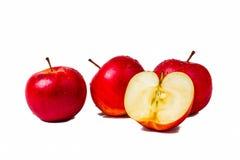 Trois pommes rouges et une demi pomme Photos libres de droits