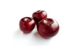 Trois pommes rouges fraîches d'isolement sur le fond blanc Image stock