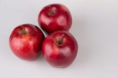 Trois pommes rouges sur le blanc Photos stock