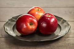 Trois pommes rouges sur une plaque de métal images libres de droits