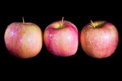 Trois pommes sur un fond noir photos libres de droits