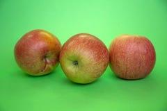 Trois pommes sur un fond vert Photos stock