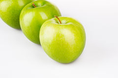 Trois pommes vertes sur le blanc Photographie stock