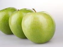 Trois pommes vertes sur le fond blanc Images libres de droits