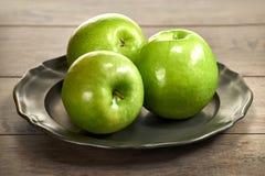Trois pommes vertes sur trois pommes rouges de plaque métallique sur un métal pl photographie stock