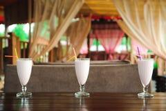 Trois pots de milkshakes roses de baie avec des pailles sur la vieille table en bois photographie stock libre de droits