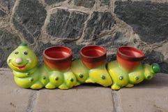 Trois pots de terre cuite de la forme d'une chenille Photographie stock libre de droits