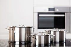 Trois pots en métal sur la fraise-mère d'induction Image libre de droits