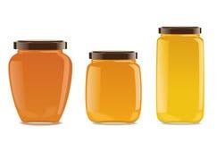 Trois pots en verre avec la confiture ou le miel Photo stock