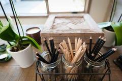Trois pots en verre de crayons affilés sur un bureau à la maison photographie stock libre de droits