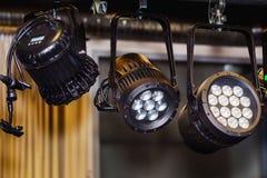 Trois projecteurs noirs sur un stege Photographie stock libre de droits