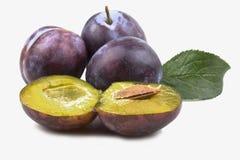 Trois prunes bleues mûres entières étroitement avec les deux moitiés Photo stock