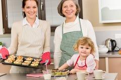 Trois rétablissements des femmes faisant cuire au four dans la cuisine Images stock