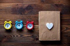 Trois réveils et livres colorés avec la forme de coeur Image stock