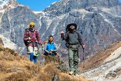 Trois randonneurs adultes marchant sur le sentier piéton en montagnes Photos stock
