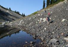 Trois randonneurs commençant vers le haut de la montagne de boucle image stock